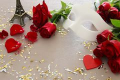 Valentine& x27;s day romantic background with beautiful bouquet of roses and masquerade white mask on wooden table.