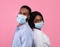 Free Valentine& X27;s Day During Covid-19 Pandemic. Black Couple Wearing Face Masks, Standing Back To Back On Pink Background Royalty Free Stock Photos - 207849928