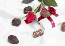 Valentines. Gift with a rose and gourmet chocolate laying on white satin Stock Image