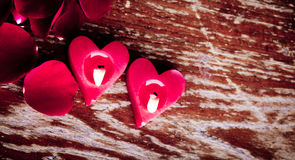 Valentines candles. And rose petals on wood background Stock Photography