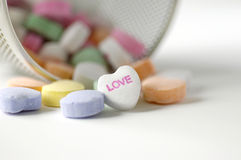 Valentines candy. Valentine candy hearts spilling from container with love message showing Royalty Free Stock Photos