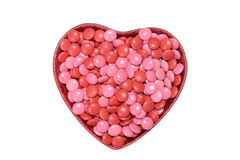 Valentines candy coated chocolate in heart bowl. Isolated valentines candy coated chocolate in heart bowl royalty free stock photography