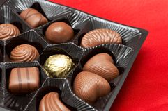 Valentines chocolates in box on red silk Stock Photos