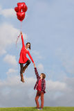 Valentines couple. Valentines girl floating with heart balloons Royalty Free Stock Image