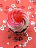 Valentines Cupcake. On red with several confetti hearts Royalty Free Stock Image