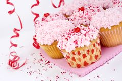 Valentines cupcakes with sprinkles. Valentine's cupcakes with pink frosting and sprinkles curly red ribbons and white background copy space selective focus royalty free stock photo