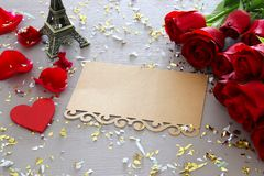 Valentines day background. Beautiful bouquet of roses next to empty letter on wooden table. Stock Photography