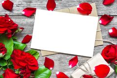 Blank white greeting card with red rose flowers bouquet and envelope with petals and gift box Royalty Free Stock Photography