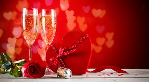 Valentines day background with champagne. Background of Valentines day celebration with champagne, rose, heart shaped present and red candies Royalty Free Stock Images