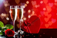 Valentines day background with champagne. Background of Valentines day celebration with champagne, rose, heart shaped present and red candies Stock Photos