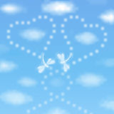Valentines day background with dragonflies. Valentine`s day background with two hearts drawn by dragonflies in a blue sky with clouds Stock Images