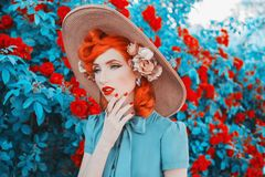 Valentines Day background. Elegant girl with red lips and nails in dress. Summer flowers. Woman think. Elegant redhead model on stock photo