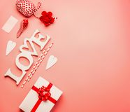 Valentines day background with flat lay of word Love, hearts, gift box with red ribbon and greeting decoration. Top view, copy space Stock Photography