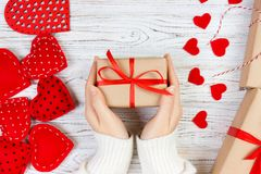Valentines Day background. girl hand give valentine gift box with a red heart inside on a white old wooden table. Valentine day.  Royalty Free Stock Image