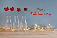 Valentines day background. Glitter hearts in the glass vases. On wooden table royalty free stock photos