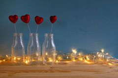 Valentines day background. Glitter hearts in the glass vases. On wooden table. Filtered and toned image stock images