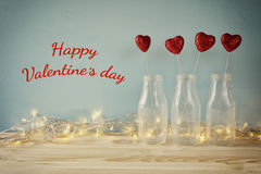 Valentines day background. Glitter hearts in the glass vases. On wooden table. Filtered and toned image royalty free stock image