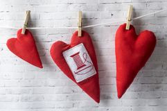 Valentines day background with handmade textile hearts. Hearts are red. Hang on the rope stock photography
