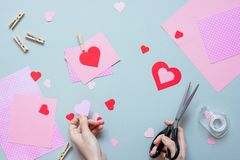 Valentines day background. Hands making Valentine card with heart and on the blue background stock image