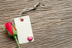 Valentines day background with heart, rose and tag on wood backg Stock Photography