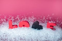 Valentines Day background. Love text in snow on pink background stock photo