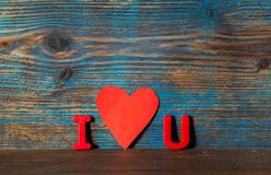 Valentines day background, magnet letters i and u and red heart Royalty Free Stock Photo