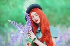 Valentines Day background. Marvelous redhead girl with long hair on lupine background. Fairytale hero. Beauty woman in mint dress royalty free stock photography
