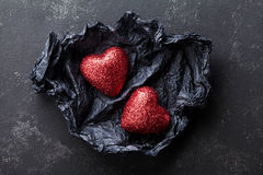 Valentines day background with pair of shiny heart in black paper from above. Stock Images
