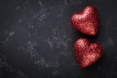 Valentines day background with pair of shiny heart on black table from above. Royalty Free Stock Image