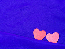 Valentines day background with red hearts on blue fabric. Love and Valentine concept Stock Photos