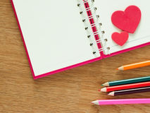 Valentines day background with red hearts, book for diary and color pencils on wood floor. Love and Valentine concept Royalty Free Stock Photos