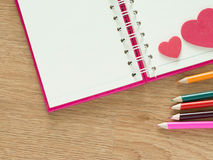 Valentines day background with red hearts, book for diary and color pencils on wood floor. Love and Valentine concept Stock Photos