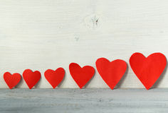 Valentines day background, red hearts in a line on a light wooden background Royalty Free Stock Image