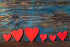 Valentines day background, red hearts in a line on a wooden background. Valentines day background, red hearts in a line on a rustic wooden background stock photo