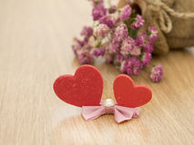 Valentines day background with red hearts on wood floor and blurred pink roses in background. Love concept Royalty Free Stock Photo