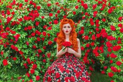 Valentines Day background. Retro girl with red lips in stylish dress with print of roses in beautiful summer garden Royalty Free Stock Photos