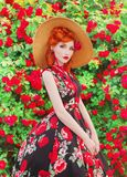 Valentines Day background. Retro girl with red lips in stylish dress with a print of roses in a beautiful summer garden. Valentine. S Day beauty redhead model in stock photo