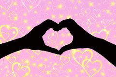 Valentines day background, silhouette of two hands making a heart shape together a pink and sparkly background with stock image