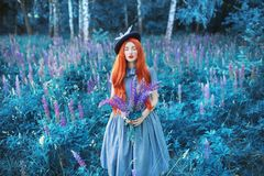 Valentines Day background. Spring lupine flower garden. Sweet perfume. Trendy girl with red lips in dress. Flower perfume. Redhead. Woman on background of royalty free stock photo