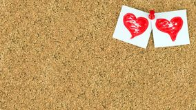 Valentines day background with two red hearts on white a pieces of paper at the right upper conner of cork brown board. Valentines day background. There are two Stock Image