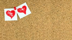 Valentines day background with two red hearts on white a pieces of paper at the left upper conner of cork brown board. Valentines day background. There are two Stock Photo