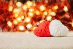 Valentines Day background with two red and white knitted fluffy heart on red golden bokeh shiny glitter background. Valentine Day. Love, romance, dating royalty free stock photography
