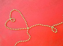 Valentines Day Background. Valentine's Day background: golden like perls in the form of a heart on a red wooden surface. Free space for a text Royalty Free Stock Photo