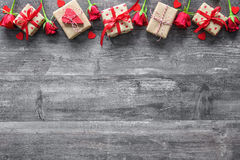Valentines day background. Valentines day vintage background with red roses and gift boxes on wooden board Stock Image