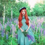 Valentines Day background. Young neat redhead girl with very long hair on lupine background. Valentines Day beauty woman. In mint dress against backdrop of royalty free stock images
