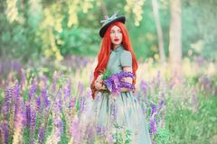 Valentines Day background. Young romantic redhead girl with very long hair on lupine background. Valentines Day beauty woman in mi. Nt dress against backdrop of royalty free stock image