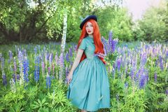 Valentines Day background. Young terrific redhead girl with very long hair on lupine background. Terrific woman in mint dress. Against backdrop of beautiful royalty free stock photos
