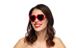 Woman with red lipstick and heart shaped shades. Valentines day, beauty and people concept - happy smiling young woman with red lipstick and heart shaped Royalty Free Stock Images