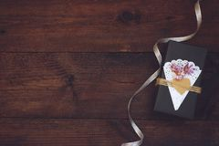 Valentines day, birthday Craft gift box with decor Black paper present box with heart, lace napkin, jute rope on wooden background. Love, romance, handmade royalty free stock photography