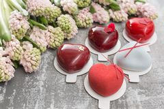 Valentines day or birthday greeting card. Lot a desserts in the form of a red heart. Pink hyacinths and dessert on. Valentines day or birthday greeting card. Lot Stock Image